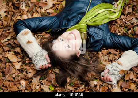 Model released, Frau liegt entspannt im Herbstlaub - woman relaxing in autumn foliage - Stock Photo