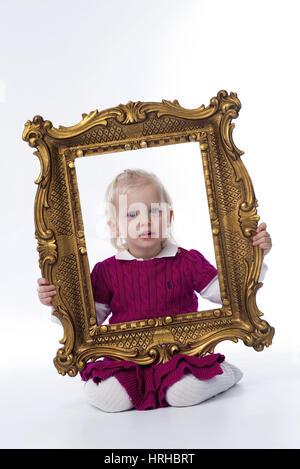 Model released, Kleines Maedchen im goldenen Bilderrahmen - little girl in golden frame - Stock Photo