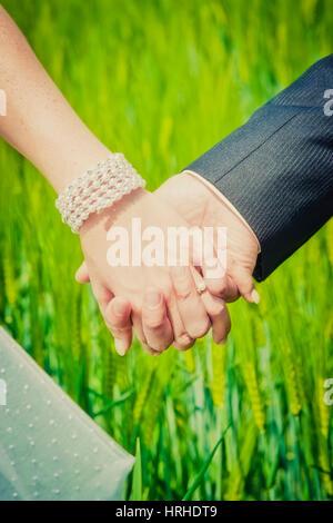 Brautpaar haelt sich die Haende - bridal couple - Stock Photo