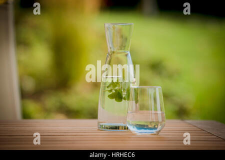 Wasserkrug- und glas mit Kraeutern - water jar with herbs - Stock Photo
