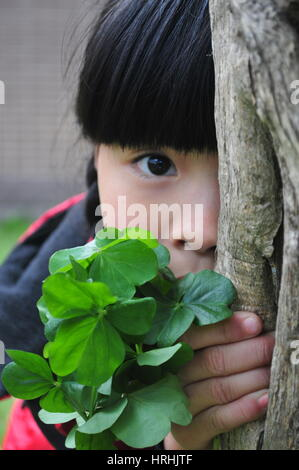 Shy Girl Behind a Tree Playing Hide and Seek - Stock Photo