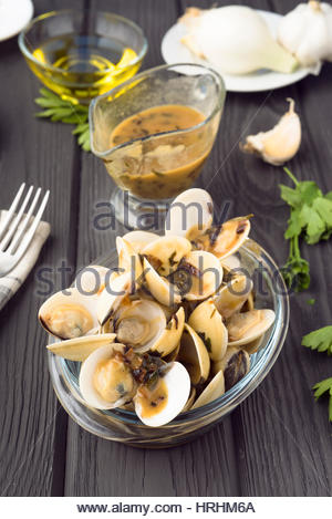 vertical view of bowl of clams in sauce and sauceboat on black wood - Stock Photo