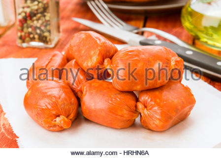 Raw red sausage on rustic wooden board - Stock Photo