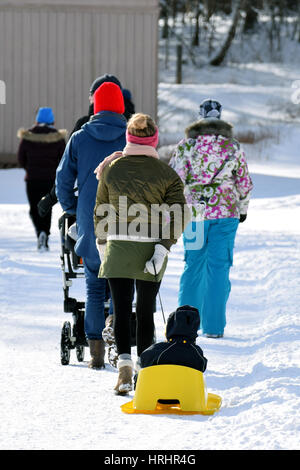 Woman pulling small child on an yellow sled. - Stock Photo