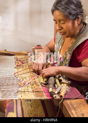 Zapotec woman weaving a rug on a floor loom in farmhouse, Teotitlan del Valle, Oaxaca, Mexico, North America - Stock Photo