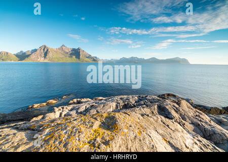 Sun shines on the blue sea and the rocky peaks at night during summer, Vikten, Nord Trondelag, Lofoten, Norway, - Stock Photo