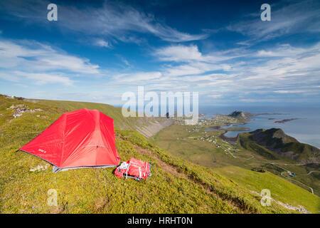 Tent on mountain ridge overlooking meadows and sea, Sorland, Vaeroy Island, Nordland county, Lofoten archipelago, - Stock Photo