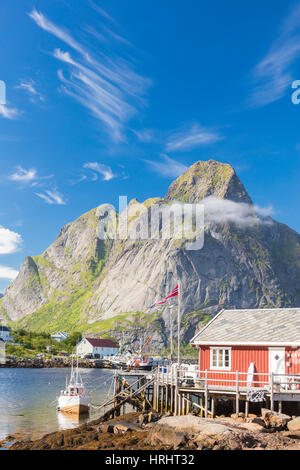 Typical house of fishermen called Rorbu framed by rocky peaks and blue sea, Reine, Moskenesoya, Lofoten Islands, - Stock Photo