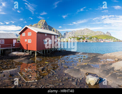 Typical house of fishermen called Rorbu reflected in blue sea, Reine, Moskenesoya, Lofoten Islands, Norway, Scandinavia - Stock Photo