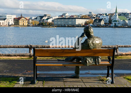 Sculpture of a man sitting on a park bench in front of Tjornin Lake and the Historic Centre of Rykjavik, Iceland, - Stock Photo