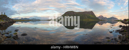 Panorama of pink clouds and peaks reflected in water at night time, Vengeren, Vagspollen, Lofoten Islands, Norway, - Stock Photo