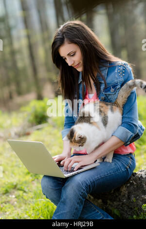 Junge Frau mit Katze sitzt mit Laptop in der Natur - woman with cat and laptop in nature - Stock Photo