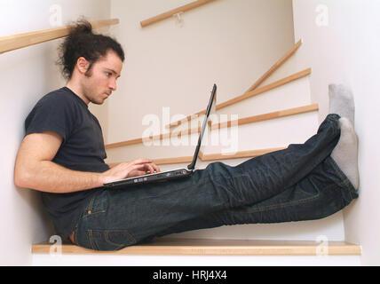 Junger Mann sitzt mit Notebook auf Stufenaufgang - young man using laptop on stairs, Symbolfotos - Stock Photo