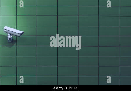 Horizontal front view of a surveillance monitoring white camera viewed from a side with green background wall of - Stock Photo