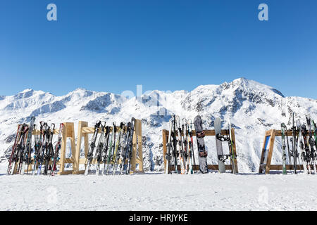 A line of skis and snowboards stored on racks outside a cafe on the slopes at Hochgurgl with the Otztal Alps in - Stock Photo