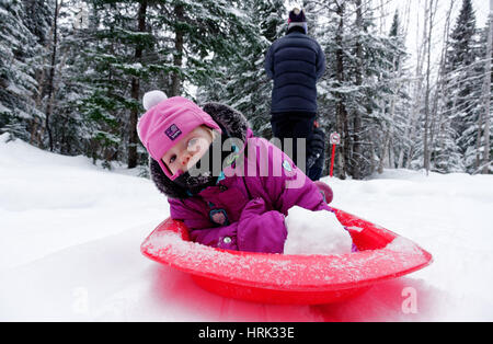 A little girl (2 yrs old) being pulled by her mother in a sledge - Stock Photo