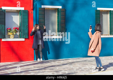 Female tourist poses for a photograph in front of bright blue and red houses at Burano - bright colors of Burano, - Stock Photo
