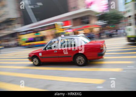 Taxi passing along street, Causeway Bay, Hong Kong Island, Hong Kong, China - Stock Photo