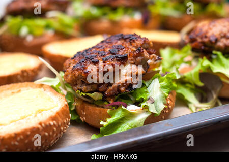 Delicious homemade hamburger with lettuce and cheese in baking tray. Homemade dinner - Stock Photo