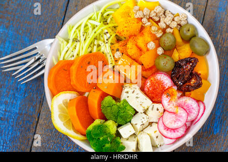 Vegan Buddha bowl - zucchini pasta, sweet potatoes, tofu with vegetables. Love for a healthy vegan food concept - Stock Photo