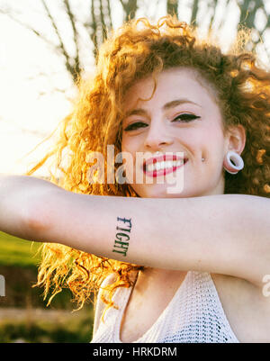 Young alternative redhead woman with piercings and tattooes enjoying the sunset at summer
