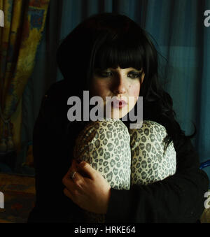Sad young woman trapped in her bedroom - Stock Photo