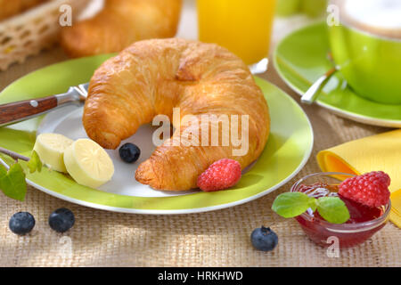 Breakfast table with a cup of cappuccino and fresh croissants with butter and jam - Stock Photo