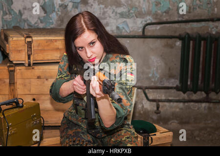 A girl with a firearm in her hands.