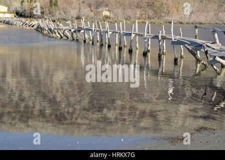 Old destroyed wooden  bridge over the river - Stock Photo