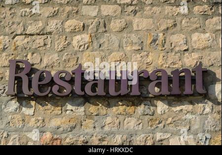 Written 'Restaurant' on the stone wall - Stock Photo