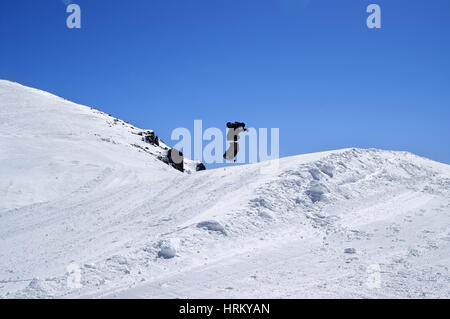 Snowboarder jumping in snow park at ski resort on sun winter day. Caucasus Mountains, region Dombay. - Stock Photo