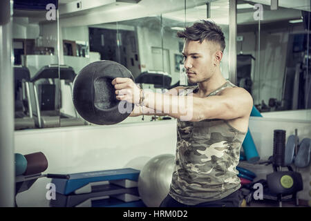 Attractive young athletic man exercising in gym, working out using kettlebell - Stock Photo