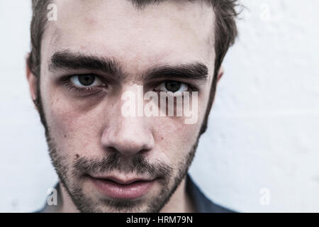 A closeup portrait of a serious looking young man. - Stock Photo