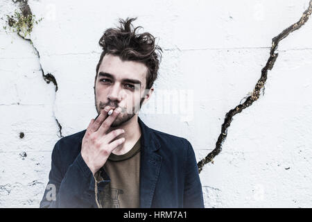 Portrait of a serious young man smoking a cigarette. - Stock Photo