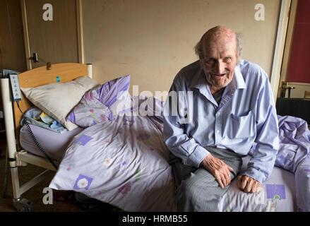 Bedridden man living alone in social housing - Stock Photo