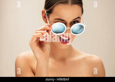 Portrait of beautiful young woman with sunglasses. Female fashion model winking with glasses against beige background. - Stock Photo