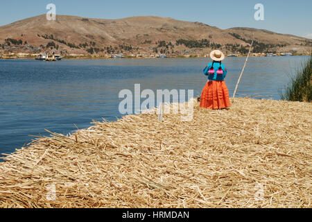A woman dressed in traditional Peruvian clothing looks out to Lake Titicaca and the city of Puno from the Uros Islands - Stock Photo