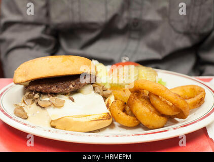 Specialty burger with mushrooms and Swiss cheese and onion rings as a side - Stock Photo