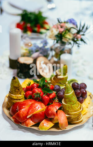 Cut fruits and berries stand served on banket table in plate - Stock Photo