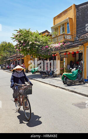 Woman rides bicycle in Hoi An Ancient Town. Quang Nam Province, Vietnam. - Stock Photo