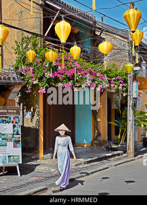 Woman in traditional Vietnamese Ao Dai dress. Hoi An Ancient Town, Quang Nam Province, Vietnam. - Stock Photo