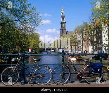 Bicycles on a bridge over Prinsengracht, with Westerkirk in distance, Amsterdam, Holland, Netherlands. - Stock Photo