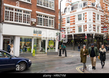 People walking in Wardour street, Soho in front of a local branch of the Japanese restaurant Wasabi. London, UK - Stock Photo