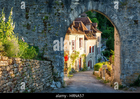 Setting sunlight on homes at entry gate to Saint-Cirq-Lapopie, Lot Valley, Occitanie, France - Stock Photo