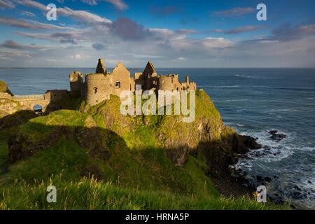 Sunrise over Dunluce Castle along northern coast of County Antrim, Northern Ireland, UK - Stock Photo