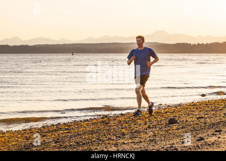 A young man running on a beach in Seattle's Discovery Park. Seattle, Washington, USA. - Stock Photo