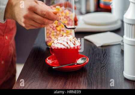 Barista is decorated  of a pieces of marshmallow on the cream in a mug of cappuccino. Close-up bright background. - Stock Photo