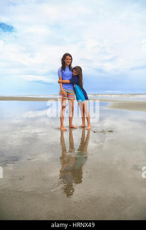 Two brunette tween sisters hug on the beach on a cloudy day. They are wearing rash guards and board shorts. - Stock Photo