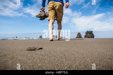 A man walking on a beach barefoot carrying his shoes, 2nd Beach, Olympic National Park Coastal Strip, Washington, - Stock Photo