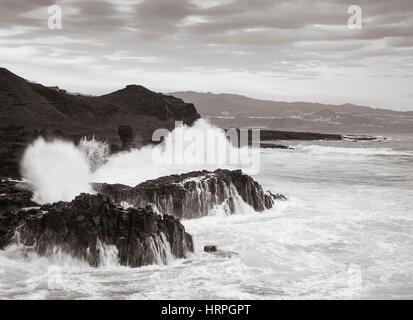 Huge waves crashing over Basalt rocks on the rugged, volcanic north coast of Gran Canaria, Canary Islands, Spain - Stock Photo